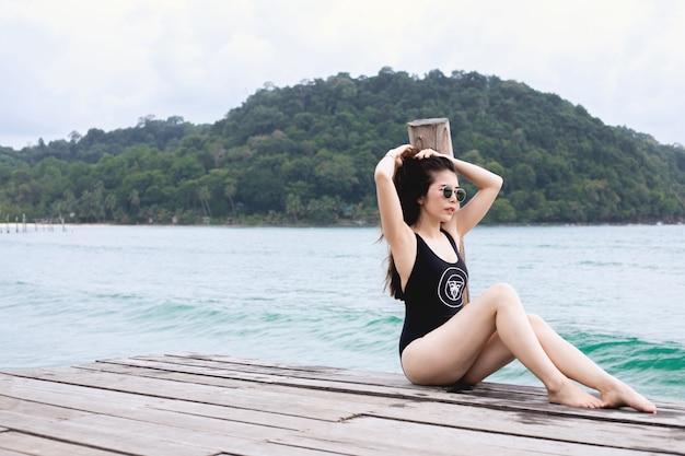 海、夏の休日の概念で桟橋のビーチで日光浴の水着の若い女性。