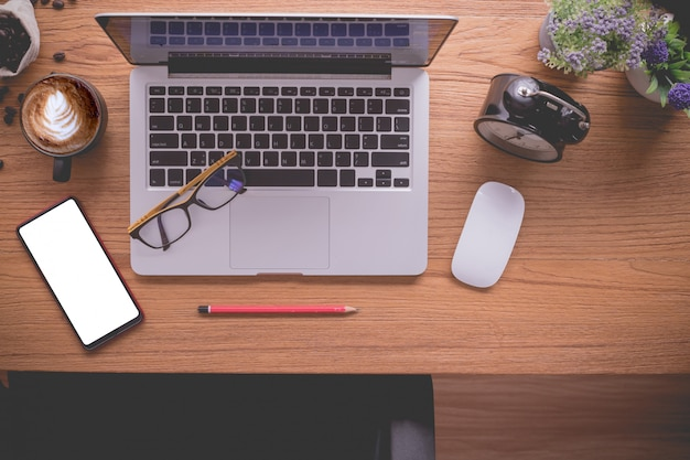 ノートパソコンと書類、ラテコーヒーカップの木製オフィステーブル。
