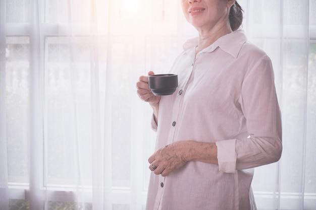 アジアの高齢者の女性が白いカーテンにコーヒーを飲む
