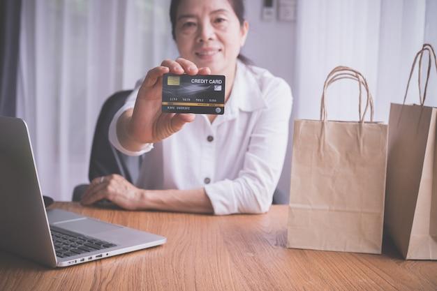 Азиатская пожилая женщина показывая насмешливую поднимающую вверх кредитную карточку, концепцию покупок онлайн.
