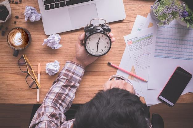 目覚まし時計、遅延支払いを保持している実業家と木のテーブルは、オフィスのテーブルの上からの眺め。