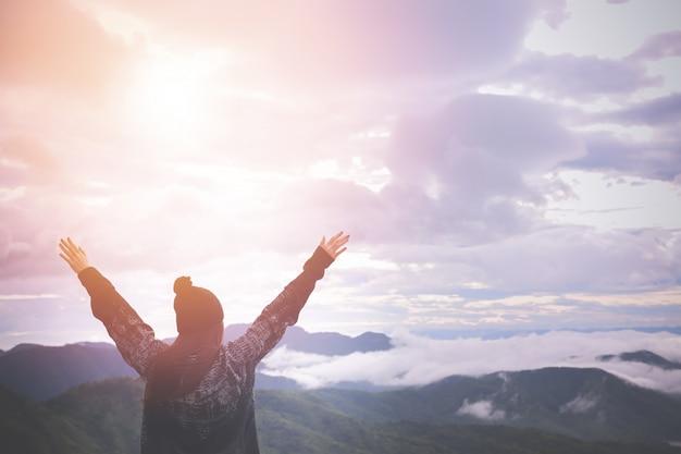 女性の背面図は、朝の風景に手を上げた。