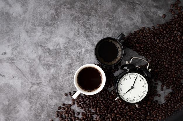 セメントテクスチャ背景に黒と白のコーヒーマグカップ。朝のコーヒーコンセプト、上記のテーブルからの眺め。