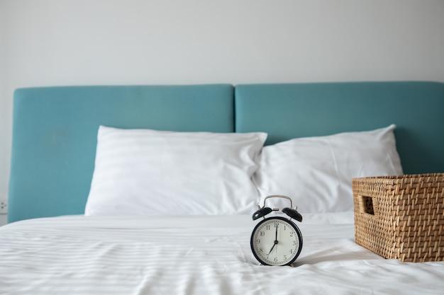 寝室のベッドの上の木製バスケットと白いベッドの上の古典的な時計。