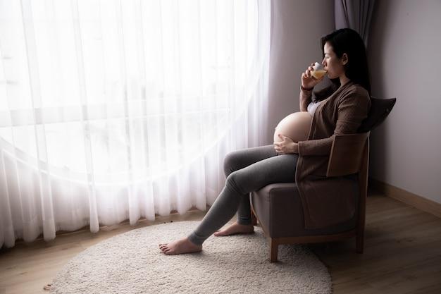妊娠、母性、人々、期待の概念、妊娠中の女性がオレンジジュースを飲みます。