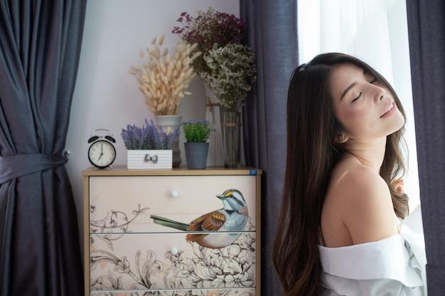 リビングルームでリラックスした笑顔の若いアジア女性。