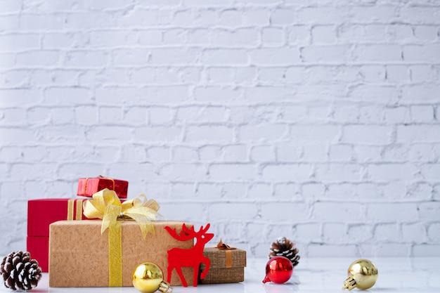 白いレンガ壁テクスチャ背景にクリスマスギフトボックス。