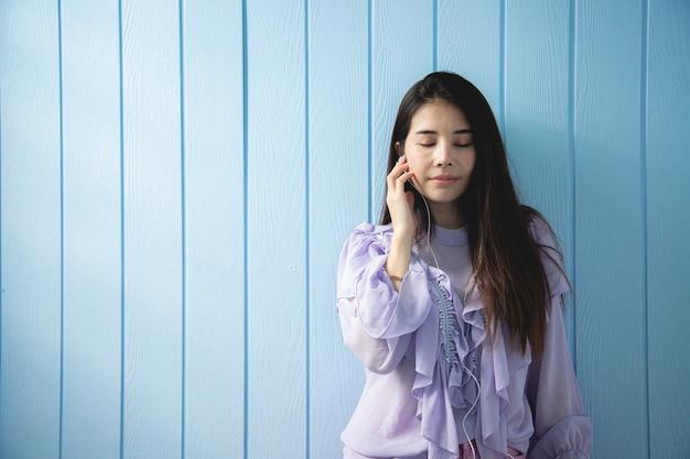 青い木製の壁で音楽を聴く若いアジア女性