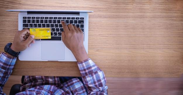 ビジネスマンは、コンピューター、オンラインビジネスコマーシャルの概念でクレジットカード番号を入力します。