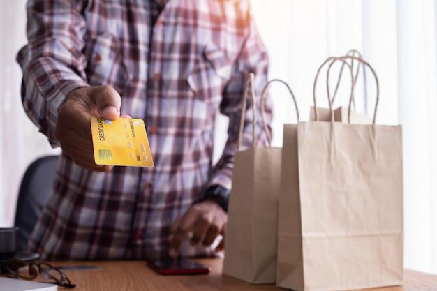 ビジネスマンはショッピングバッグとクレジットカートのモックアップを表示します。