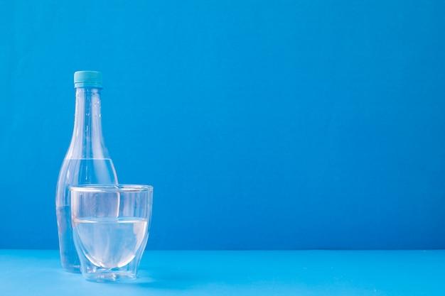 Стекла воды на голубой предпосылке.