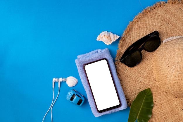 Плоские лежал путешественник аксессуары на синем фоне с копией пространства смарт-телефон, летний фон.