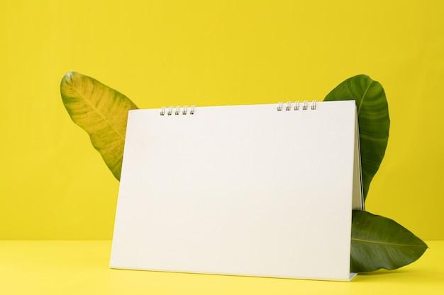 Бумага календаря пустого экрана на желтой предпосылке с рамкой листьев.