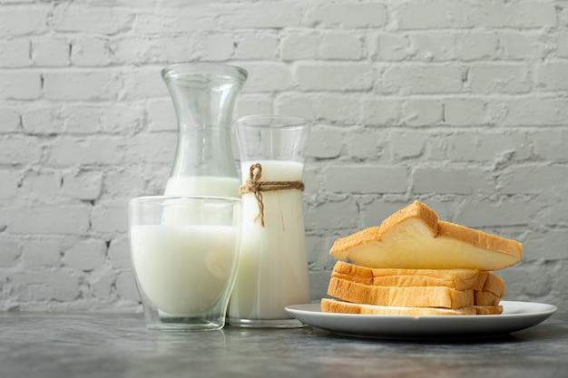 Стакан молока и ломтик хлеба на кухонном столе.