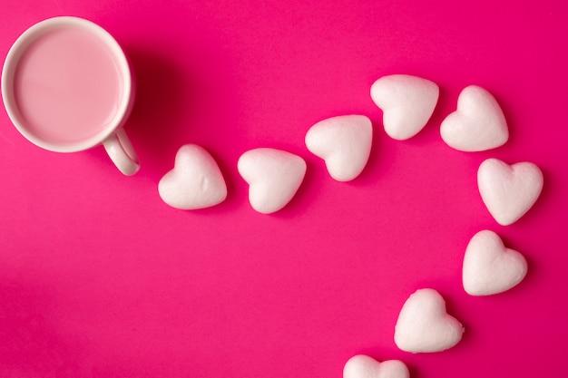 Чашка клубничного молока с символом формы сердца на розовый.