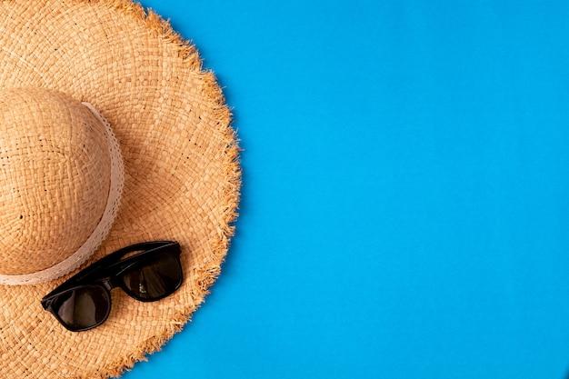 Деревянная женская шляпа и солнцезащитные очки на синем