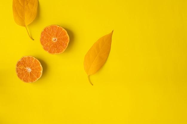 Отрезанный оранжевый плодоовощ на желтом цвете, взгляд сверху.