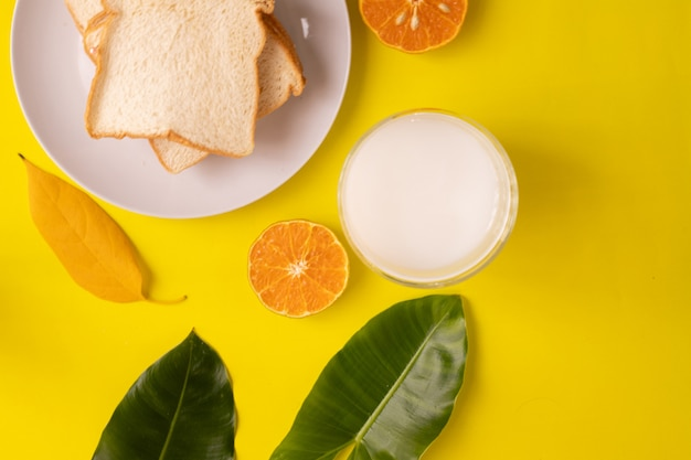 Стол для завтрака с нарезанным хлебом и стакан молока на желтом