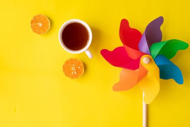 Радужная вертушка на желтом с горячим напитком и нарезанным апельсином