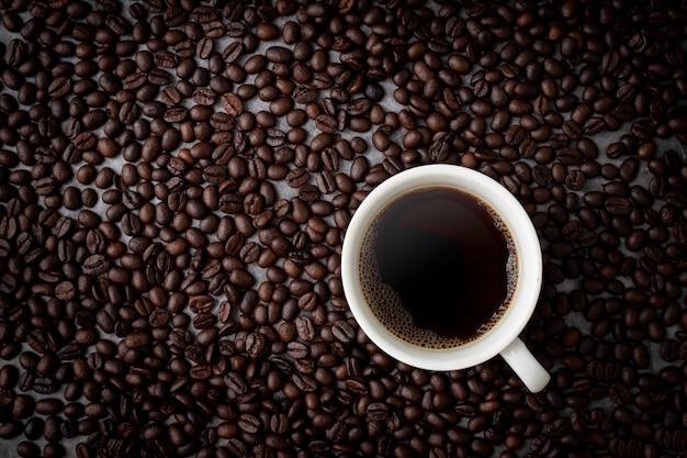Кофейная чашка с кофе в зернах вид сверху таблицы