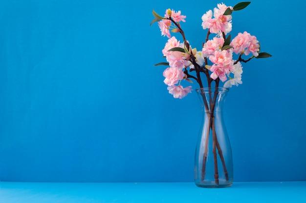 Стеклянная ваза с розовым цветком сакуры на синем фоне