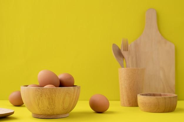 Яйца и деревянная посуда на желтом фоне