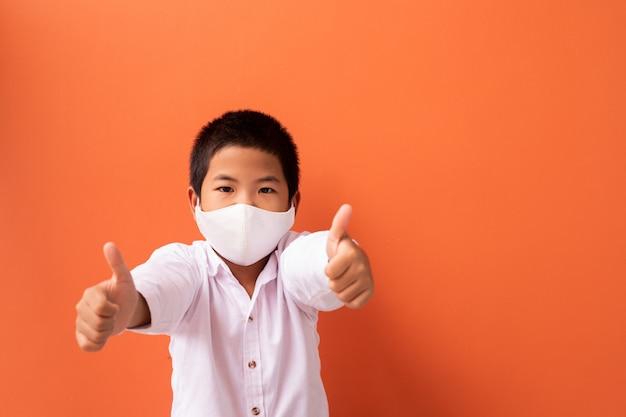 アジアの子供たちはオレンジ色に分離された良いサイン手を繋いでいるマスクを着用します