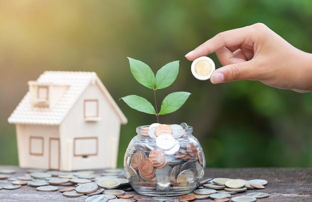 手とコインのコンセプトは、家のためにお金を節約します
