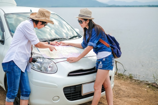 Пара путешественник, стоя перед автомобилем и глядя на карту рядом с озером во время отпуска.