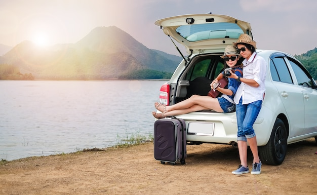 Пара путешественник, сидя на хэтчбек автомобиля и наслаждаясь видом природы