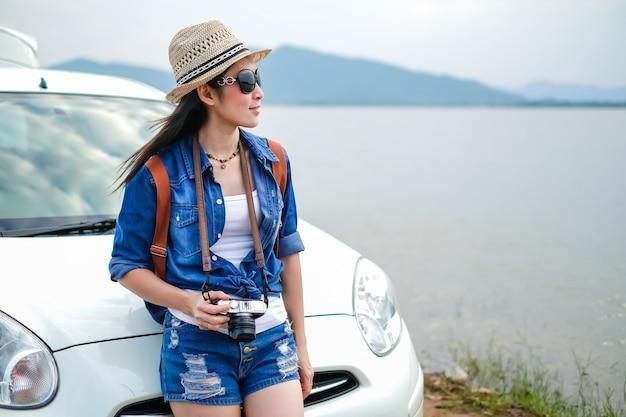 Женщина путешественника, стоящего рядом с автомобилем, и смотрит на природу у озера