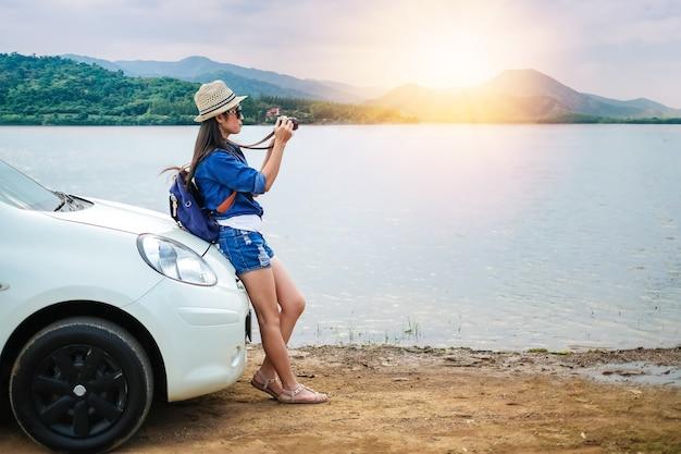 Женщина-путешественник, стоящая рядом с автомобилем и фотографирующая вид на природу у озера