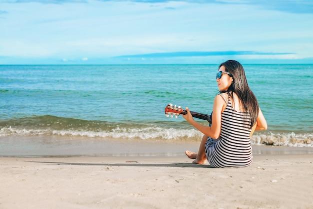Женщина путешественник счастлив на пляже. леди держит гитару на море и расслабляется на ней