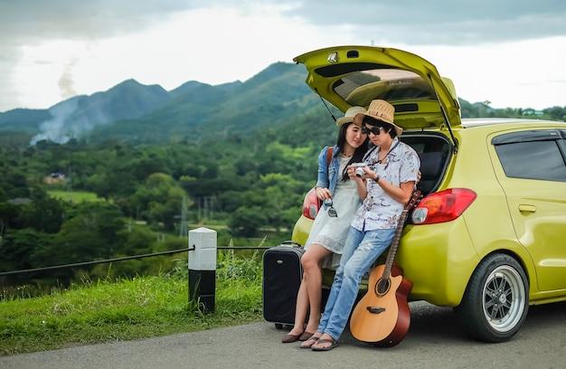Пара путешественника, сидящего на хэтчбек автомобиля и глядя на картинку