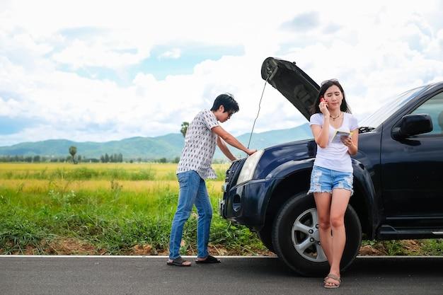 アジアカップルの旅行者は車に関する問題を抱えています。