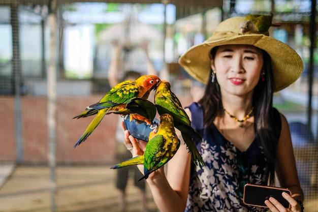 Женщина-путешественница, кормящая многих попугаев вручную в клетке для птиц
