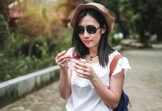 美しい女性旅行者がアイスクリームを食べる