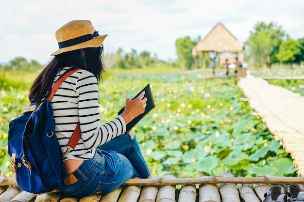 Женщина-путешественница, сидящая и читающая книгу на деревянном мосту