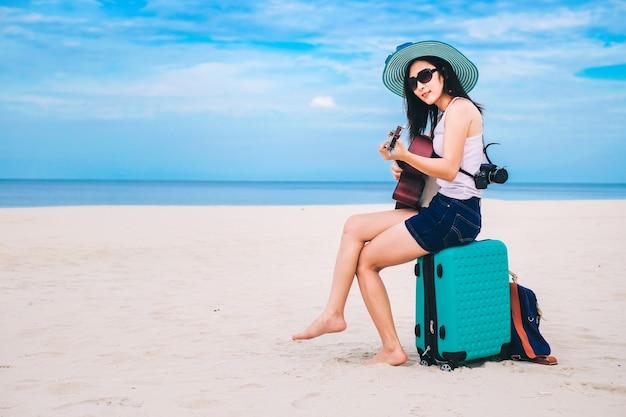 女性の旅行者は荷物を持っていて、ビーチでギターを弾いています