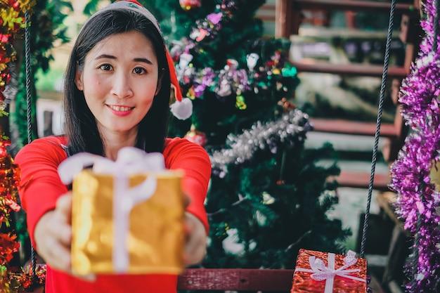 アジアの女性とクリスマスフェスティバルのギフトボックス。