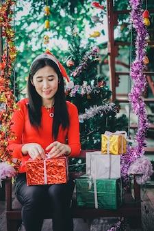 クリスマスフェスティバルで多くのギフトボックスを持っている女性。