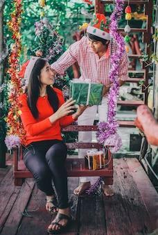 クリスマスと新年の祭りで女性に贈り物を与える男。