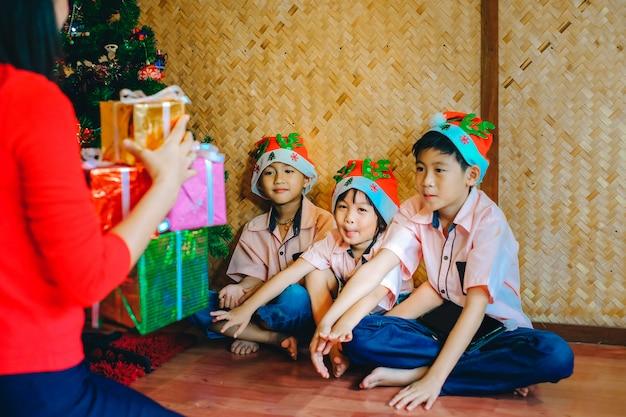クリスマスフェスティバルで子供たちに贈り物をする母親。