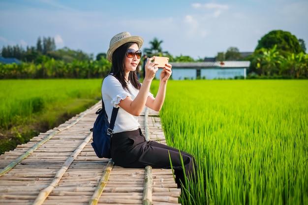 女性の旅行者は彼女の休日に緑の田んぼを楽しんでいます。