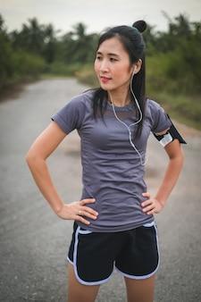 スポーツウェアでアジアの美しい女性が道を走る前に暖まる。
