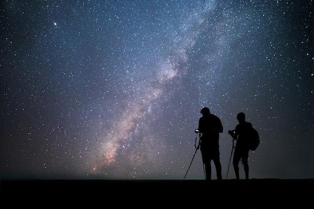 Мужчина фотограф стоит возле камеры и фотографирует млечный путь и звезды