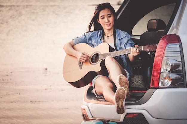 アジアの旅行者がハッチバック車を座っているとギターを弾く