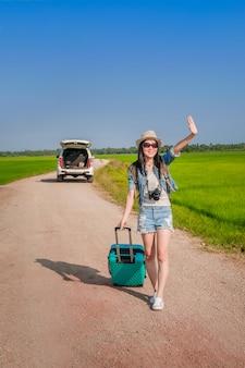 女性旅行者が手荷物を牽引して道を歩いて。