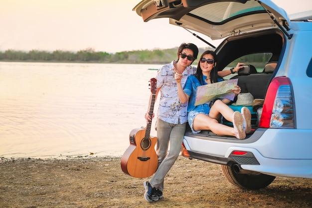 Пары путешественника сидя на хэтчбеке автомобиля и играя гитару около дороги во время праздника.