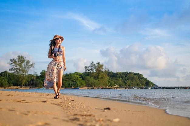 女性旅行者、ビーチの上に立って、海の景色の写真を撮る